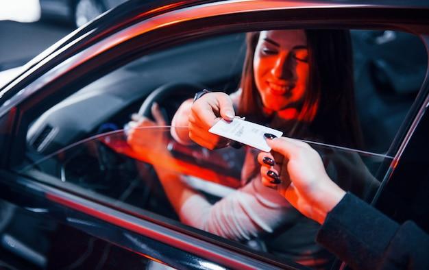 Jonge vrouw zit in een gloednieuwe moderne auto met creditcard.