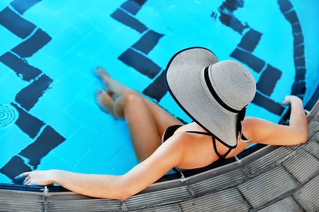 Jonge vrouw zit in het zwembad met een hoed op