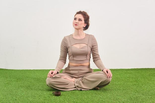 Jonge vrouw zit in lotushouding voor meditatie en kijkt dromerig op lichte achtergrond