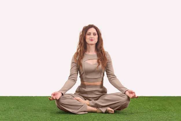 Jonge vrouw zit in lotushouding voor meditatie op lichte achtergrond