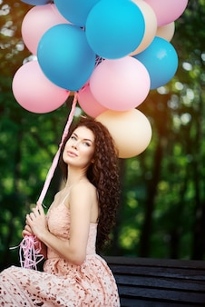 Jonge vrouw zit in park op bankje en houdt veelkleurige ballonnen in handen