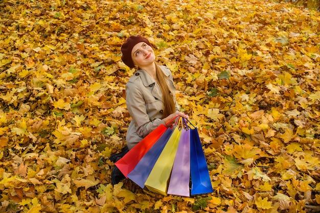 Jonge vrouw zit in park op herfstbladeren met veelkleurige pakketten in handen. grote herfstverkoop.