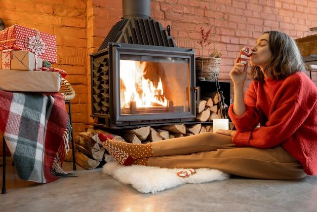 Jonge vrouw zit met een kerstsnoep bij de open haard. huis gezelligheid en warmte tijdens de wintervakantie