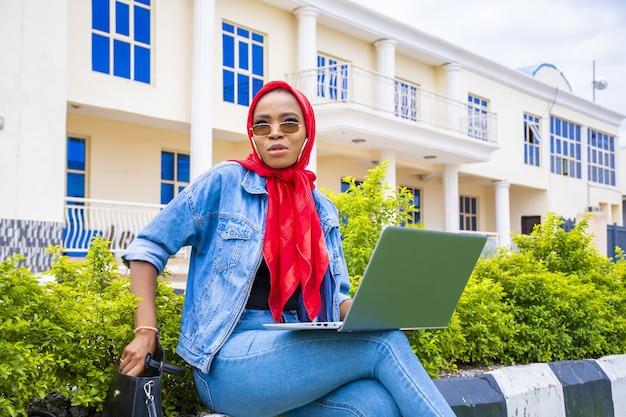 Jonge vrouw zit met haar laptop in een park