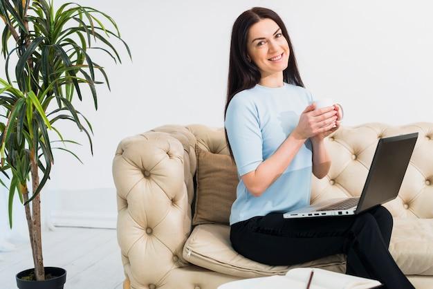 Jonge vrouw zit met koffie en laptop op de bank