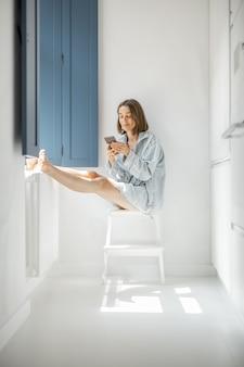 Jonge vrouw zit met mobiele telefoon alleen bij het raam in een lichte kamer thuis. zelfisolatie, eenzaamheid, meisje voelt zich thuis kalm en ontspannen
