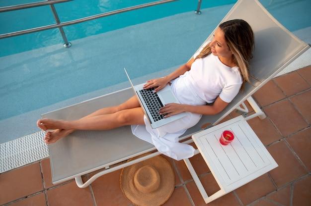 Jonge vrouw zit naast het zwembad met een laptop op schoot