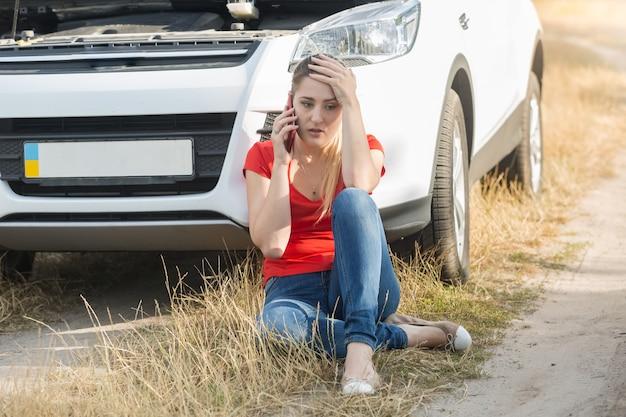 Jonge vrouw zit naast kapotte auto en roept om hulp