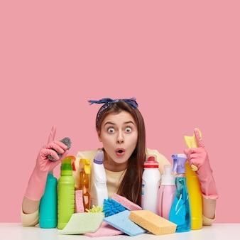 Jonge vrouw zit naast schoonmaakmiddelen