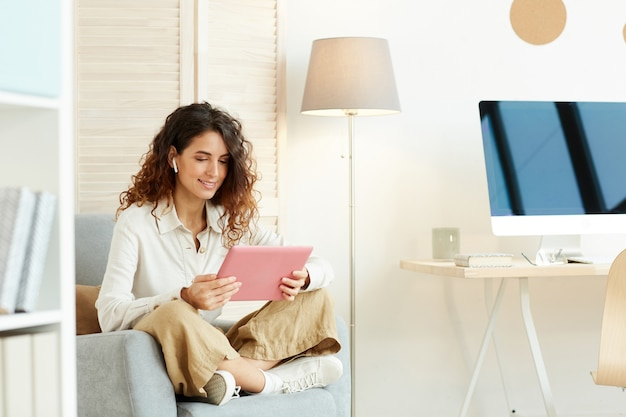Jonge vrouw zit ontspannen in haar fauteuil en werkt met behulp van tabletcomputer en internet
