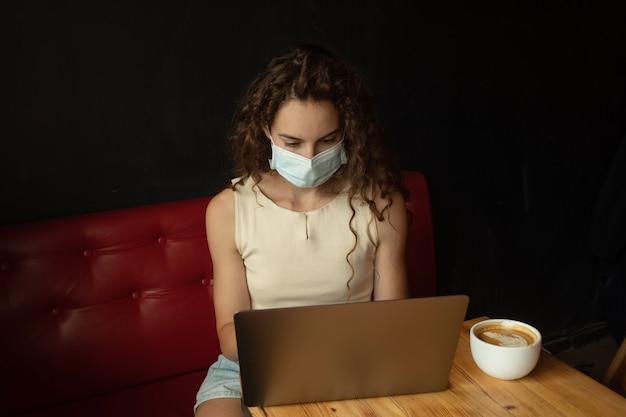 Jonge vrouw zit op coffeeshop en werkt op laptop met gezichtsmasker