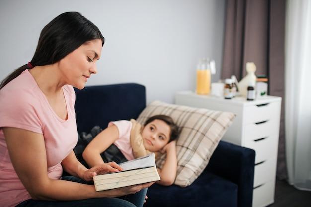 Jonge vrouw zit op de bank in de kamer en lees boek aan haar zieke dochter. kind dat daar ligt en luistert. ze kijkt naar moeder. vrouw is geconcentreerd op lezen.
