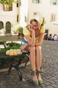 Jonge vrouw zit op de bank in de schaduw van een boom met een zakje citroenen