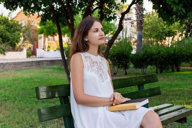 Jonge vrouw zit op de bank in het park en denkt na over wat ze heeft gelezen