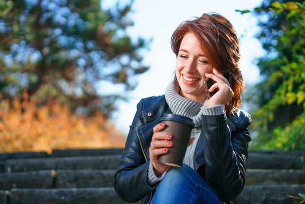Jonge vrouw zit op de trappen in een herfst park met koffie in haar handen