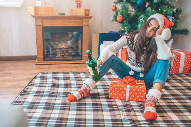 Jonge vrouw zit op de vloer en slaapt. ze houdt een groene fles alcohol in de hand. tussen haar benen zit een doos met cadeautje.