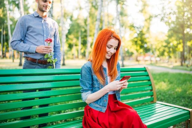 Jonge vrouw zit op een bankje, man met roos staat erachter. romantische ontmoeting van liefdepaar in zomerpark