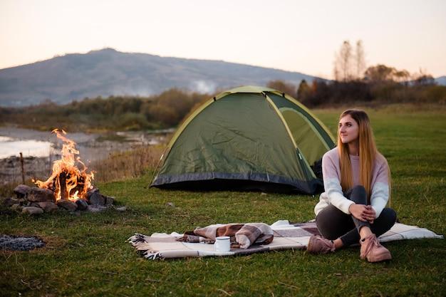 Jonge vrouw zit op een deken op het gras in de buurt van groene tent en vreugdevuur