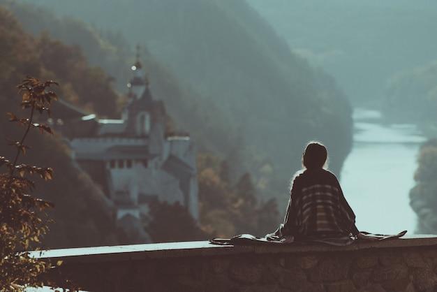 Jonge vrouw zit op een heuvel. bergen, tempel en rivier in de verte