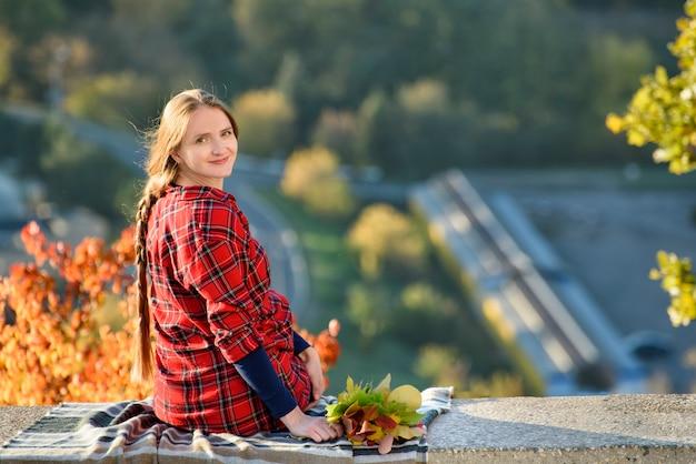 Jonge vrouw zit op een heuvel met uitzicht op de stad. achteraanzicht