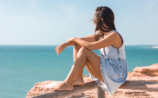 Jonge vrouw zit op een plank en kijkt overdag naar de zee