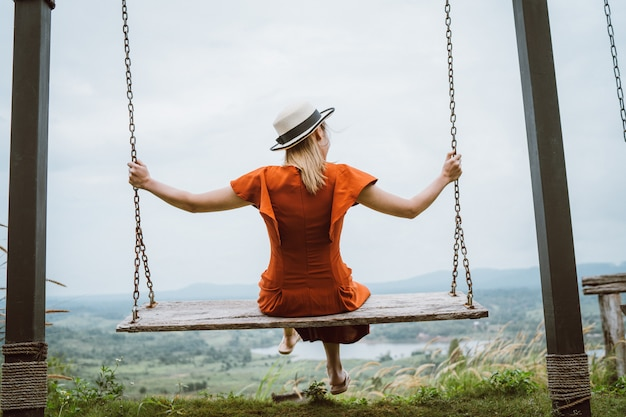 Jonge vrouw zit op een schommel