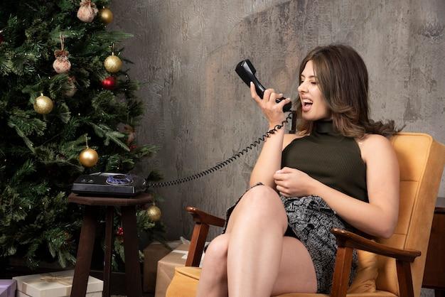 Jonge vrouw zit op een stoel en praat met iemand bij de kerstboom