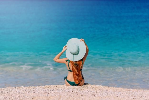 Jonge vrouw zit op het strand met haar rug naar de camera en kijkt naar zee