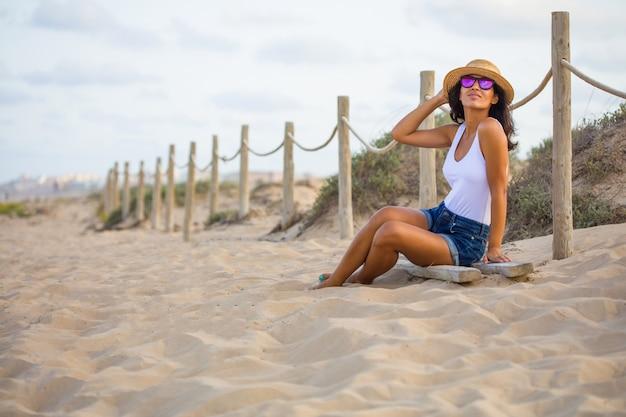Jonge vrouw zit op het strand