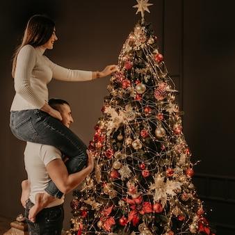 Jonge vrouw zit op rug schouders van man en versiert een kerstboom hangt ornamenten