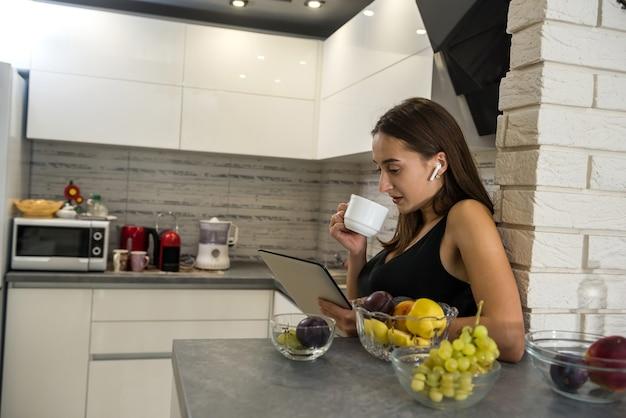 Jonge vrouw zit vooraan opengeklapte laptop en koffie drinken in haar keuken. lekker thuis genieten