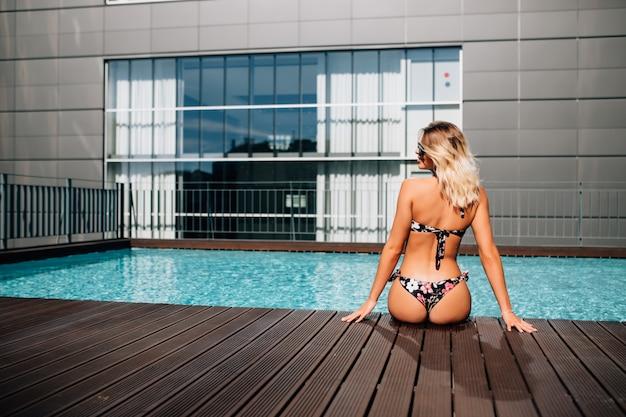 Jonge vrouw zitten bij zwembad