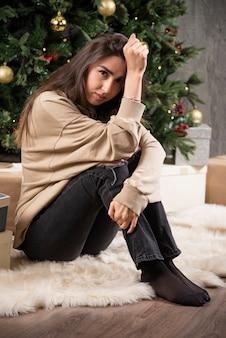 Jonge vrouw zitten en poseren in de buurt van de kerstboom.