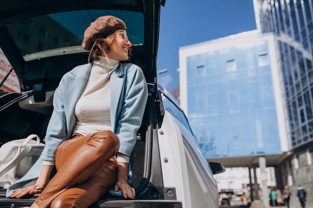 Jonge vrouw zitten in de achterkant van de auto praten aan de telefoon