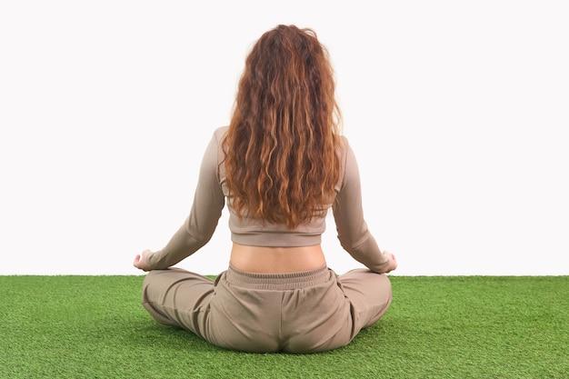 Jonge vrouw zitten in lotuspositie voor meditatie op lichte achtergrond, achteraanzicht
