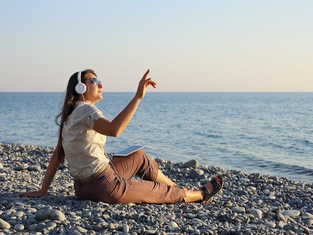 Jonge vrouw zitten luisteren naar muziek en handgebaar tonen op kopie ruimte