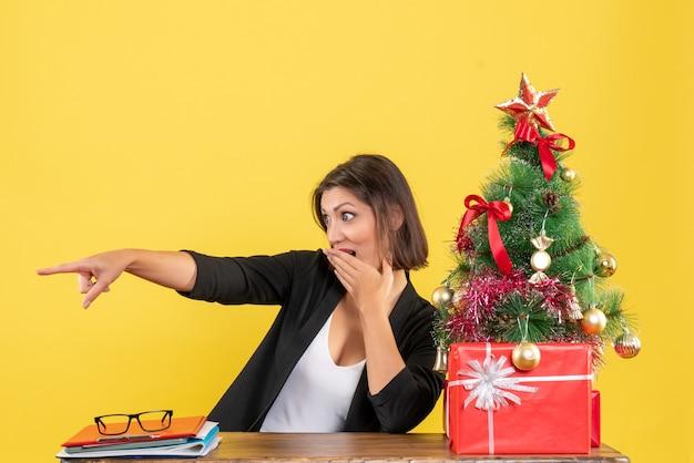 Jonge vrouw zittend aan een tafel en wijst iets aan de rechterkant in pak in de buurt van versierde kerstboom op kantoor op geel