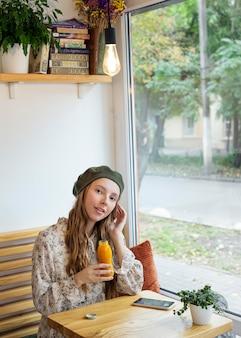 Jonge vrouw zittend aan tafel met vers sap fles