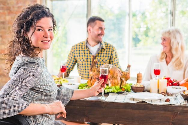 Jonge vrouw zittend aan tafel tegenover grijs vrouw en man