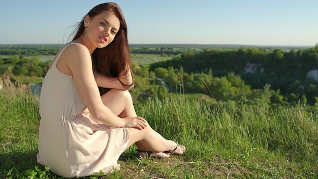 Jonge vrouw zittend door een klif buiten op de natuur. aantrekkelijk meisje met het witte kleding openlucht stellen. vrouwelijk model poseren in een veld een zonnige zomerdag.
