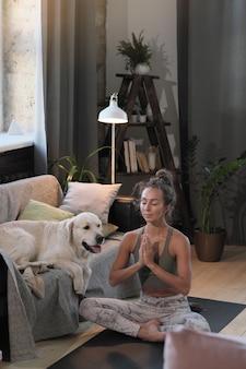 Jonge vrouw zittend in lotushouding met haar ogen dicht en ontspannen tijdens meditatie thuis