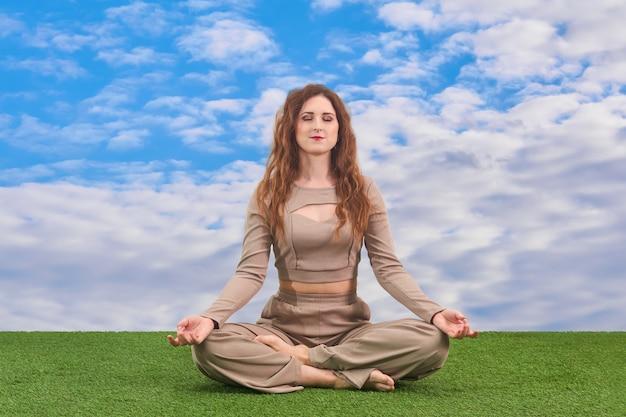 Jonge vrouw zittend in lotushouding voor meditatie op hemelse achtergrond