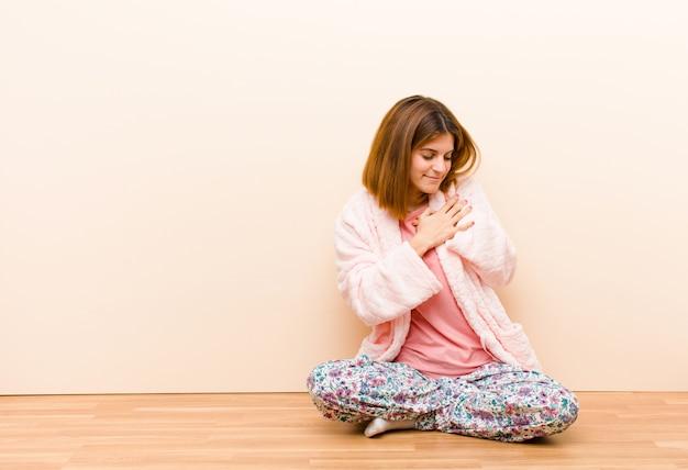 Jonge vrouw, zittend om thuis te zitten pyjama's kijken verdrietig, gekwetst en met een gebroken hart, beide handen dicht bij het hart houdend, huilend en depressief