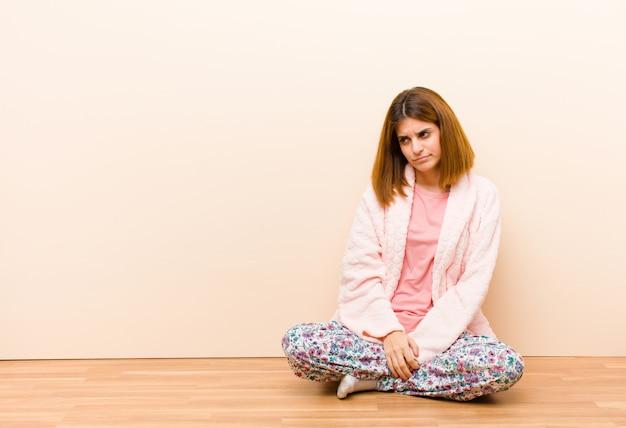 Jonge vrouw, zittend om thuis te zitten pyjama's voelen verdrietig, boos of boos en kijken naar de kant met een negatieve houding, fronsen in onenigheid