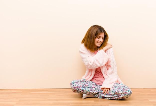 Jonge vrouw, zittend om thuis te zitten, pyjama's voelen zich angstig, ziek, ziek en ongelukkig, lijden aan een pijnlijke buikpijn of griep