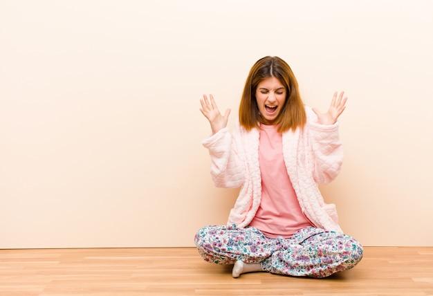 Jonge vrouw, zittend om thuis te zitten pyjama's woedend schreeuwen, gestrest en geïrriteerd voelen met handen omhoog in de lucht zeggen waarom ik