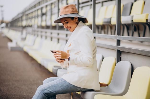Jonge vrouw zittend op de arena stoelen en praten over de telefoon