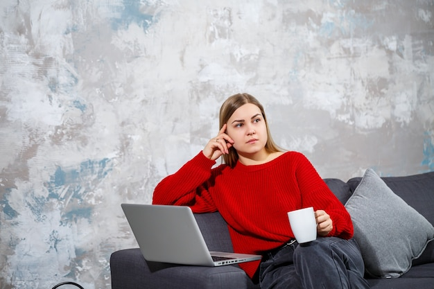 Jonge vrouw zittend op de bank kijken naar het scherm van de laptop. een gemotiveerde, thuiswerkende vrouwelijke student-freelancer die online op een computer werkt.