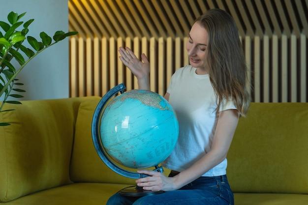 Jonge vrouw zittend op de bank thuis met een wereldbol, kiest een reisroute