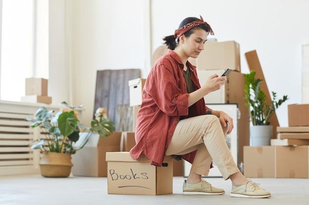 Jonge vrouw zittend op de doos en met behulp van haar mobiele telefoon bestelt ze de auto om dingen te vervoeren